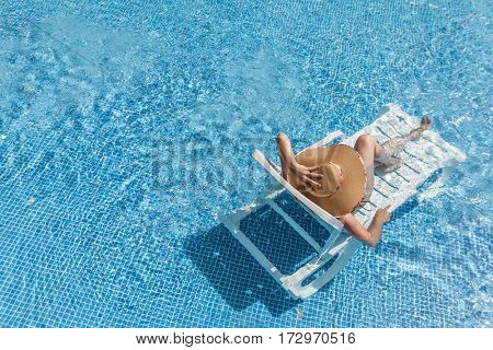 Woman enjoying her summer vacation at the swimming pool