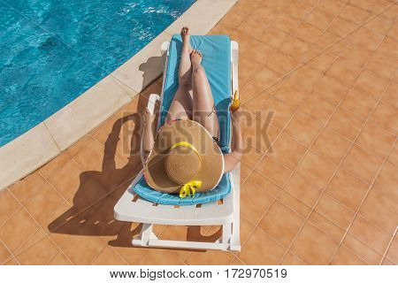 Top view of a woman in hat resting in the edge of a swimming pool