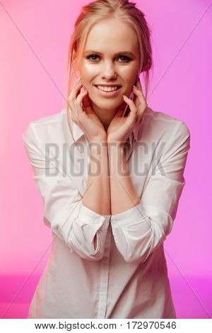 Picture of young cheerful lady dressed in white shirt standing and posing over pink background. Looking at camera.