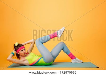 Full length of serious young sportswoman lying and working out on mat over yellow background
