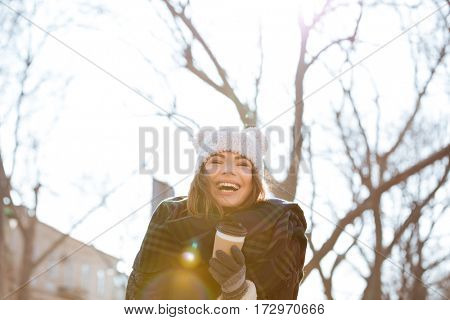 Cheerful charming young woman drinking coffee and laughing outdoors in autumn