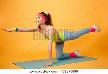 Cheerful attractive young fitness woman training and exercising on mat over yellow background