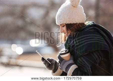 Happy charming young woman in hat and gloves using cell phone outdoors in autumn