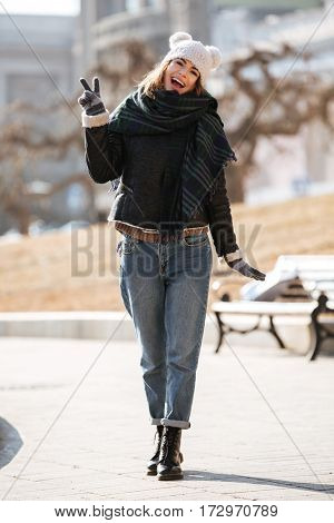Smiling attractive young woman walking and showing peace sign in the city in autumn