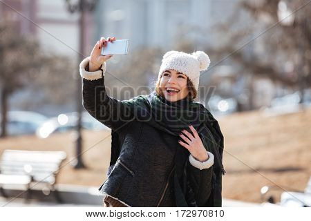 Cheerful attractive young woman taking selfie with mobile phone in the city