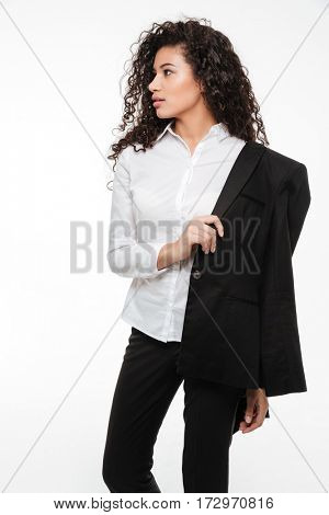 Portrait of curly african young businesswoman standing and looking away over white background