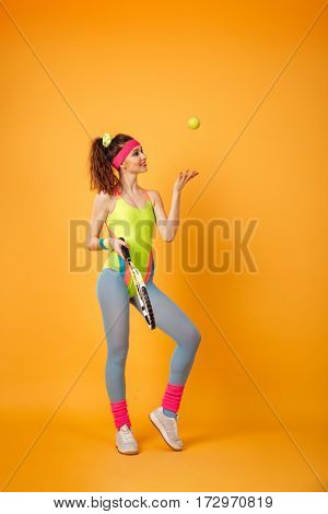 Full length of smiling attractive woman athlete playing tennis