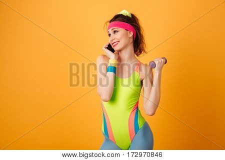 Smiling lovely young sportswoman working out with dumbbells and talking on mobile phone