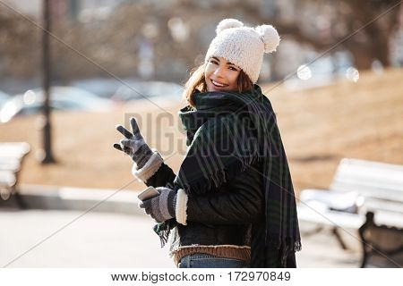 Smiling attractive young woman standing and showing peace sign outdoors in autumn