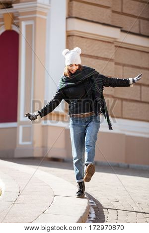 Smiling charming young woman walking on border in the city
