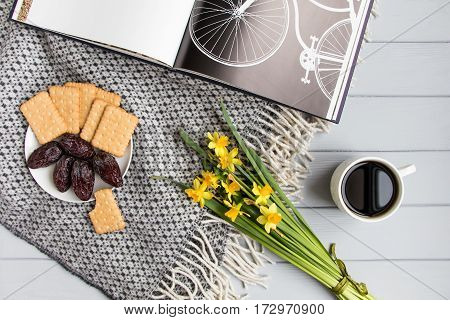 Cup of coffee cracker biscuit cookies dry date fruits and daffodil flowers. Cozy home composition with book about bicycles on a plaid on wooden floor. Top view flat lay