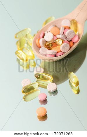 Full wooden spoon of pills. Pharmacy background on mirror table. Tablets on a black background. Pills. Medicine and health. Vitamin and oil capsules сlose up. Different kind of pills