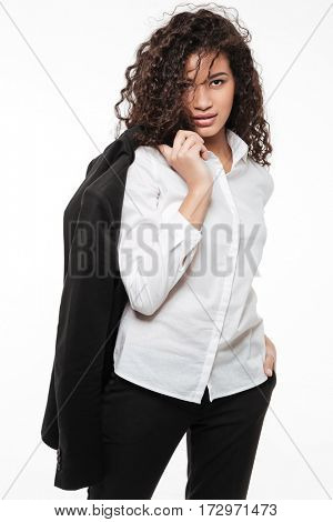 Attractive african young businesswoman standing and holding jacket on shoulder over white background