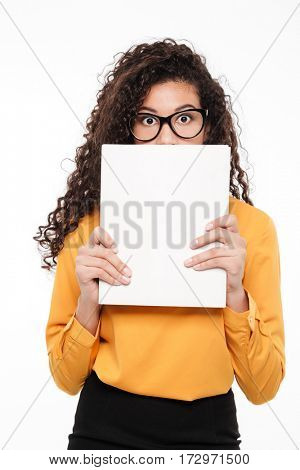 Embarrassed shy african young businesswoman hiding her face behind blank paper over white background