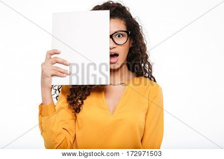 Astonished african young businesswoman in glasses covered half face with blank paper sheets over white background