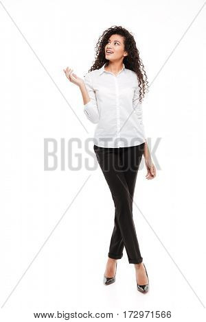 Photo of attractive young curly african woman standing and posing over white background. Looking aside.
