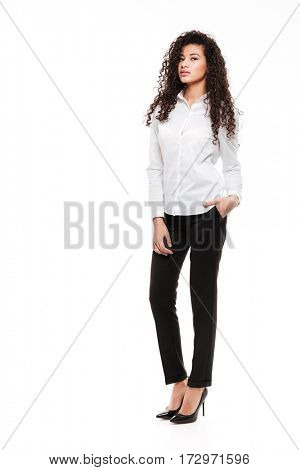 Photo of incredible young curly african lady standing and posing over white background. Looking at camera.