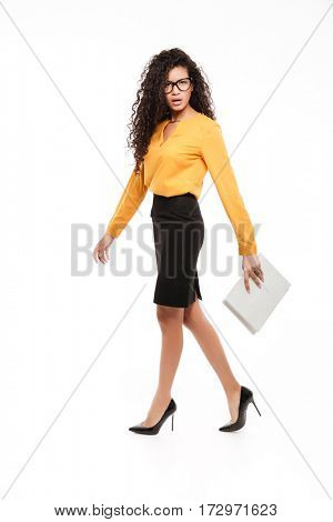 Photo of beautiful young curly african lady over white background with documents. Looking at camera.