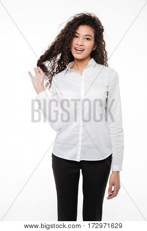 Photo of amazing young curly african woman standing and posing over white background. Looking at camera.