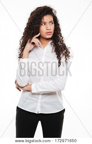 Photo of confused young curly african lady standing and posing over white background. Looking aside.