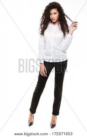 Image of pretty young curly african lady standing and posing over white background. Looking at camera.