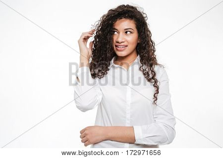 Image of pretty young curly african woman standing and posing over white background. Looking aside.