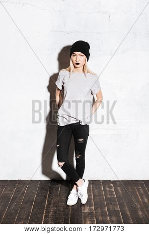 Full length of serious modern young woman with black lips in hat standing over white background