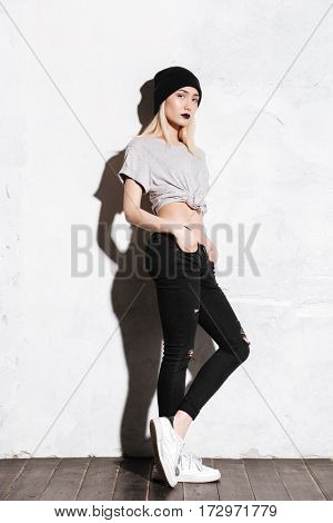 Full length of attractive young woman in black hat standing and posing over white background