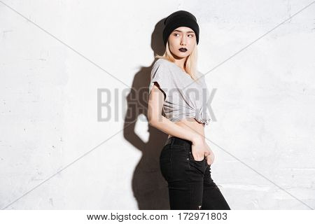 Beautiful young woman with black lips standing with hands in pockets over white background