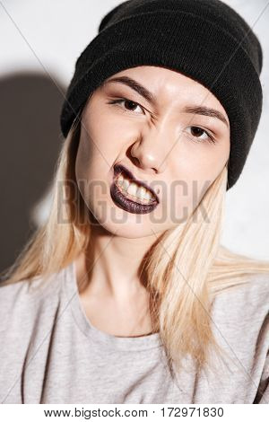 Vertical image of Young Hipster woman in black hat showing grimace over gray background