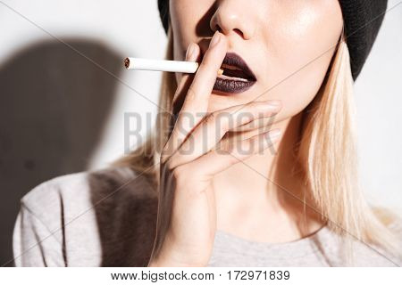 Closeup of sensual young woman with black lipstick smoking cigarette over white background