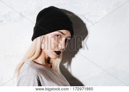 Side view of Young Hipster in black hat looking at camera