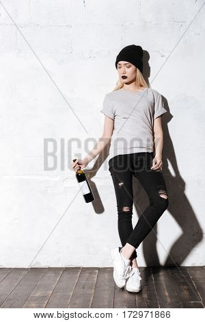 Full length portrait of Calm Hipster girl which posing near the wall with bottle of wine