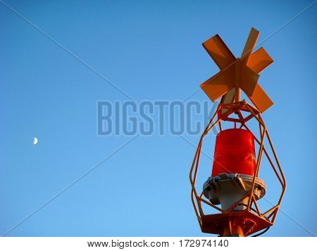 Vivid red beacon, lighthouse, day and the moon against blue sky. With place your text, background use