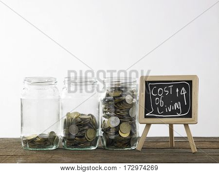 Blackboard with words cost of living increase and three saving jars from little coins ,half to full.