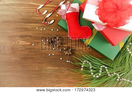 Stack of Christmas gifts with toy boot and decorations on wooden background