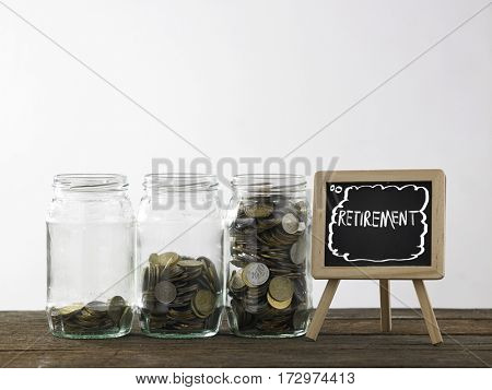 Blackboard with words retirement and three saving jars from little coins ,half to full.