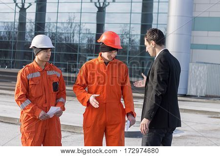 boss or Chief handshaking with workers engineers after work. Good job. Business modern background
