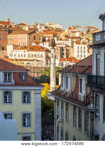 Column of Pedro IV on Rossio Square (Pedro IV Square) in Lisbon Portugal with surrounding architecture.