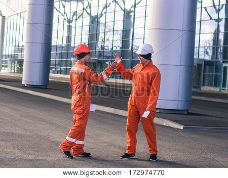 team of young engineers giving high five after work. They have envelops with salary in hands. Business modern background