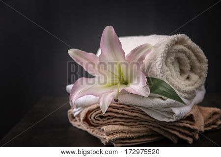 Beautiful spa composition with towels and lily flower on dark background