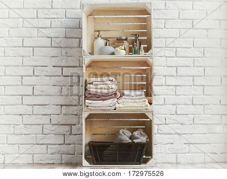 Towels and body care products in shelf made of wooden crates