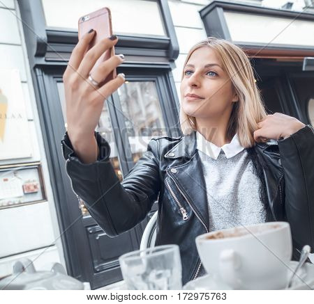 Young trendy girl taking selfie photo outdoors.