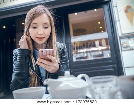 Young woman using smartphone and sitting in a cafes