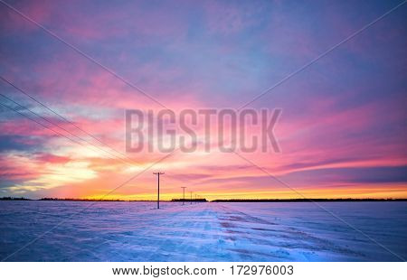 A orange yellow and purple sunset over a snow swept countryside gravel road dividing agriculture fields in a barren rural landscape