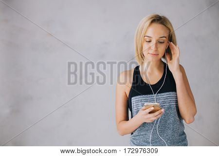 Beautiful young woman in sports wear and earphones is listening to music using a smartphone. She is scrolling her track list. Isolated. Close up