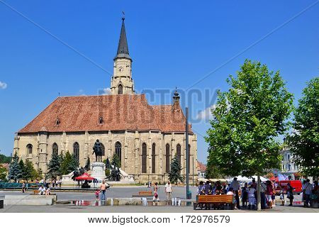 CLUJ-NAPOCA ROMANIA - AUGUST 4 2012: St. Michael's Roman Catholic Church built in gothic style and Matthias Corvinus monument in Unirii Square.