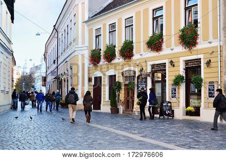 CLUJ-NAPOCA ROMANIA - cca NOVEMBER 2014: People walk on a narrow street with cobblestone pavers in the old historic town center.