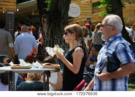 CLUJ-NAPOCA ROMANIA - JULY 9 2016: Young woman in the foreground eats fast food at a table surrounded by people having a snack at the Street Food Festival in central park Cluj. Vendors in stalls sell tasty fast food from different cultures.
