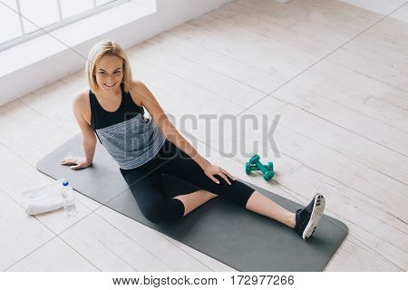 Attractive slim female doing stretching exercises on black mat in modern bright fitness center. Weary but smiling girl looking at camera. She is tired and happy at the same time